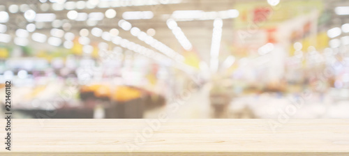 Leinwandbild Motiv Wood table top with supermarket grocery store blurred defocused background with bokeh light