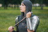 Medieval girl warrior, in a chain mail hood with a sword in his hand. A woman in European armor. Viking. Fantasy - 221475707