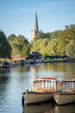 wooden edwardian boats moored up together in a typical English river scene in early autumn or fall with church in background - 221479347