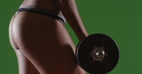 Closeup of healthy athletic female weightlifter's buttocks on green screen - 221490395