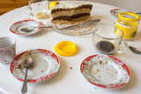 Dirty dishes on the table, homemade cake in the background - 221492512