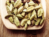 Green cardamom pods heap on wooden spoon - 221505717