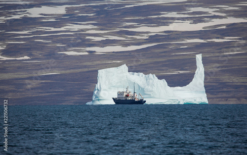 ship in front of a large iceberg