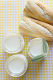 three jars with Greek yoghurt and a crispy French baguette - 221512769