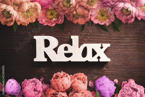 "Leinwanddruck Bild word ""relax"" on wooden background with many flowers"