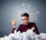 Young businessman sitting behind crumpled paper with drawings of gears and steam over his head - 221520783