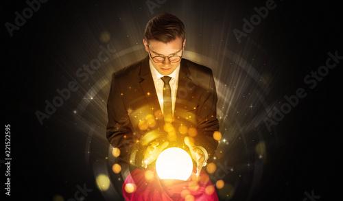Leinwanddruck Bild Gorgeous businessman sitting with sparkling magic ball in his lap