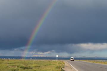 Rainbow over road with car near Qinghai Lake, China