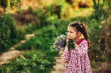 Portrait of a girl in the field . A child on a country walk in the field with flowers
