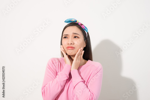 Foto Murales Oh no! Human emotions concept. Close up portrait of confused beautiful woman on white background. Young scared girl touch one's face with hands and look aside