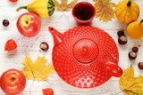 Autumn tea drinking. red textured teapot ,cup of tea with apples, chestnuts and yellow leaves on a light shabby chic background.Cozy autumn mood - 221536344