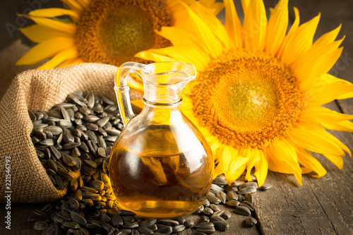 Fototapeta Closeup photo of sunflower oil with seeds on wooden background. Bio and organic product concept.