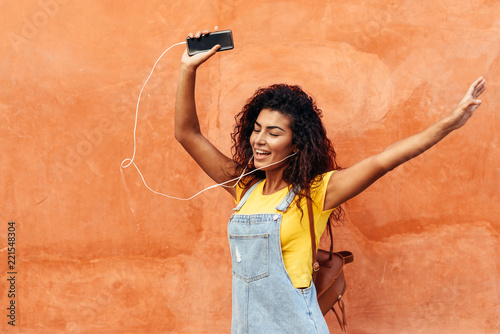 Leinwanddruck Bild Young Arab woman listening to music with earphones outdoors