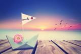 Papierboot am Strand zum Sonnenuntergang - 221550712