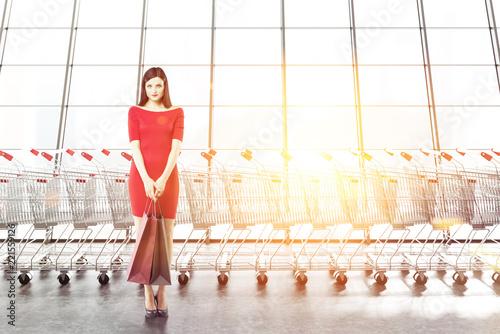 Leinwanddruck Bild Woman with paper bags, row of supermarket trolleys