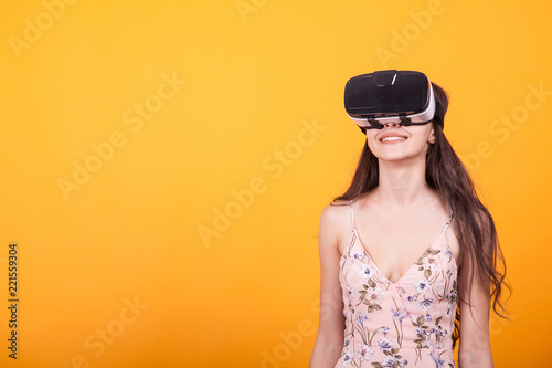 6348a7c9c865 Happy girl getting experience using VR headset glasses of virtual reality  in studio over yellow background