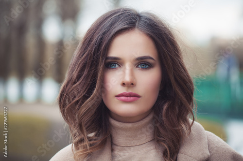 Leinwanddruck Bild Young woman with wavy hair and makeup outdoor, face closeup