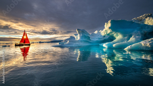 Greenland midnight sunset with heavy clouds mirror panorama with red sail ship and sun
