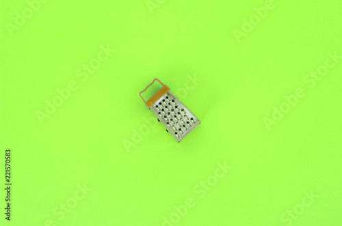 Leinwandbild Motiv Stainless steel grater lies on a pastel colored paper. Kitchen accessories. Tools for cooking. Flat lay top view