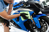 A man cleaning motorcycle with cloth. Selective focus. - 221571787