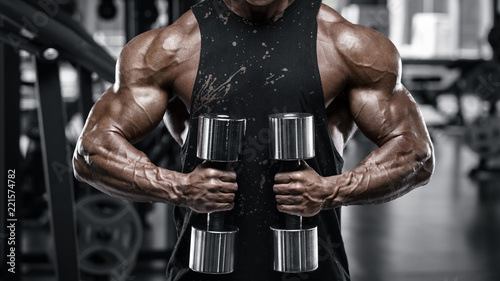 Wall mural Muscular man bodybuilder working out in gym. Strong man doing exercise