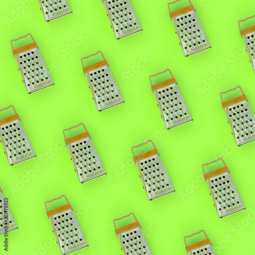 Leinwandbild Motiv Small stainless steel graters lies on a pastel colored paper. Kitchen accessories. Tools for cooking. Flat lay top view