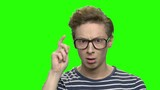 Surprised teenage boy with glasses. Portrait of amazed caucasian teenager. Green screen hromakey background for keying. - 221587177
