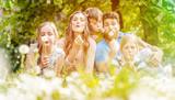 Familie mit drei Kindern sitzt in einer Wiese mit Löwenzahn und Pusteblumen