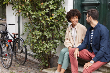 Outdoor shot of couple of hipsters have recreation, sit on threshold of cafe, leave bikes on stop, have friendly talk about hobbies, dressed in casual clothes, enjoy spare time at street. Lifestyle