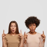 Isolated shot of mixed race women with surprised expression notice plane in sky, stand closely to each other, isolated over white background with copy space for your promotional content. Diversirty - 221592535