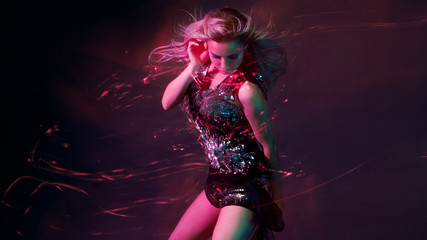 Bright and stylish young woman dancing in club, color light, motion effects © Ulia Koltyrina