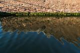 alte Backsteinmauer, die sich in einem Kanal in Comacchio, Italien, spiegelt - 221607777