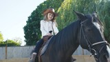 Pretty little girl in hat riding a black mare on the arena. 4K - 221607918