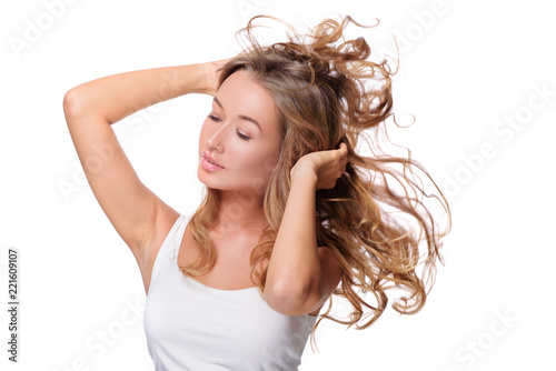 Portrait of beautiful cheerful girl with flying curly hair  over white background.
