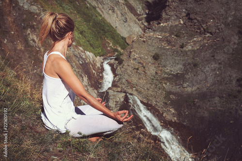 Poster Woman in yoga positiion looks at waterfall