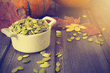 Pumpkin seeds with autumn decoration, toned photo - 221613145