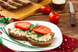 Sandwich with cottage cheese, green onions and to tomatoes, rye bread in a white plate, on a wooden table. Ingredients - 221616939