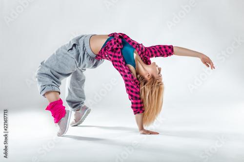 Leinwanddruck Bild Young beautiful slim girl dancing on a white studio background
