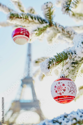 Fototapeta Christmas tree covered with snow near Eiffel tower