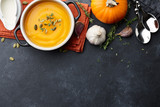 Pumpkin soup with thyme herb, cream and pumpkin seeds served in black bowl, top view - 221626315