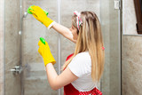 Young and happy woman cleaning house bathroom
