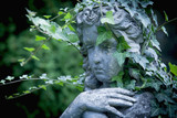 Antique sculpture of an angel with ivy against  dark background - 221628906