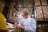 Young female worker is looking at documents with satisfaction in a storage room. - 221632713