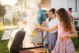 Happy grandfather is teaching his beautiful granddaughters how to make barbeque. - 221633945