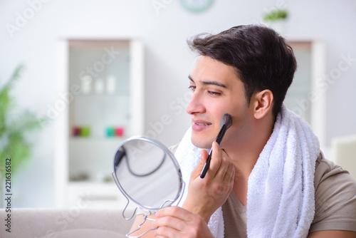 Leinwanddruck Bild Handsome applying clay mask on face