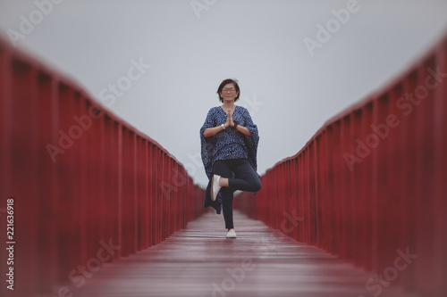 Poster asian woman playing yoga pose on red wooden bridge