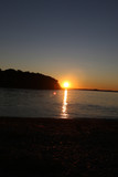 The sun setting in the summer behind a hill and in an inlet of water in Massachusetts.  - 221637761