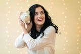 Young woman with a piggy bank on a shiny lights background - 221640358