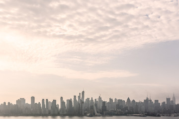 New York City midtown Manhattan skyline panorama view from Boulevard East Old Glory Park over Hudson River on a misty morning.