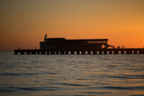 Bright orange sunset over the sea pier of the city. - 221643151